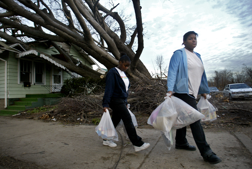 Courtney Johnson, left, helps Ebony Logan move groceries out of her home on East Laurel Street. Logan, a junior at Southeast High School, was home  when the tornado toppled the tree onto the front of her house. Ted Schurter/The State Journal-Register