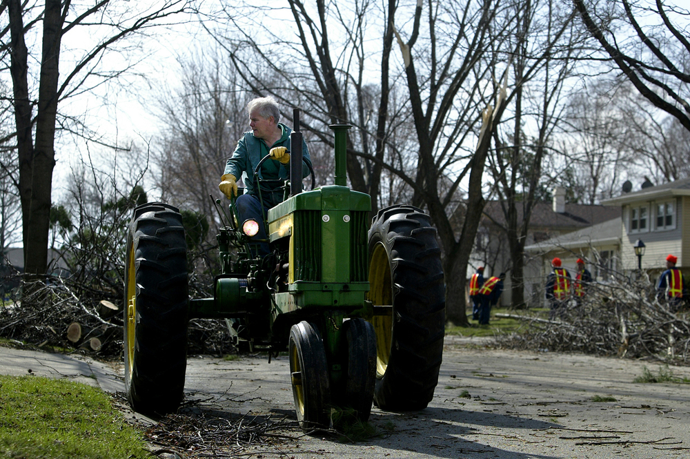 "Dan McClelland puts his circa 1955 John Deere Model 520 tractor to work helping move downed trees at the intersection of Lindenwood Drive and Westchester Boulevard Monday, March 13, 2006. ""It's kind of like snow removal,"" said Dan McClelland. If a neighbor needs help you just do it."" File/Jonathan Kirshner/The State Journal-Register"