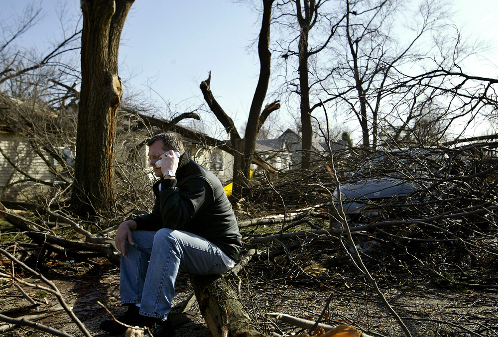 "Joe Pattie makes a call to his insurance company from the front yard of his home in the 1800 block of Vernon. ""Power went off and then about a minute later we heard it, our ears were popping and then came the crashes,"" said Joe Pattie. ""It was probably 30 seconds, but it seemed like an hour."" File/Jonathan Kirshner/The State Journal-Register"
