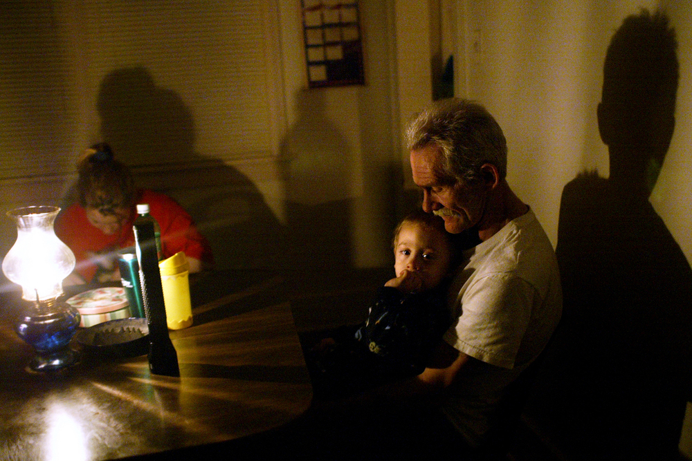 Bob Shepherd watches over his 23-month-old grandson Jesse Shepherd by the light of an oil lamp in his home in the 1800 block of S. 14th Street. File/ Jonathan Kirshner/The State Journal-Register