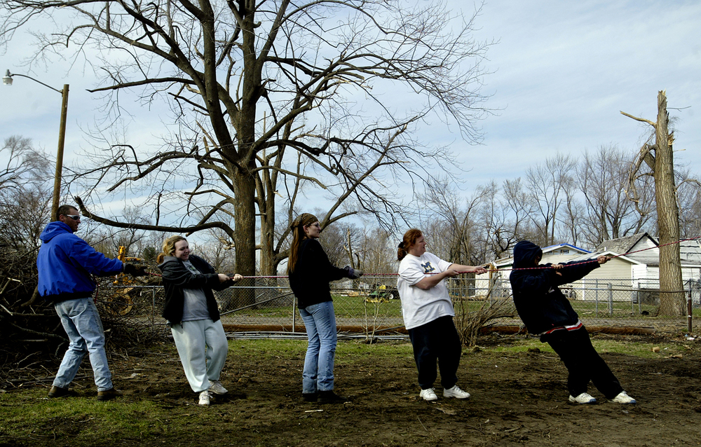 Corey Caillier, Ashlee Cody, Missy Fry, Terri Falzone and J.R. Gullo hold on tight as they apply tension to help pull over a tree being cut down in Falzone's backyard on the 2000 block of Spruce Street  Wednesday, March 15, 2006. File/Jonathan Kirshner/The State Journal-Register