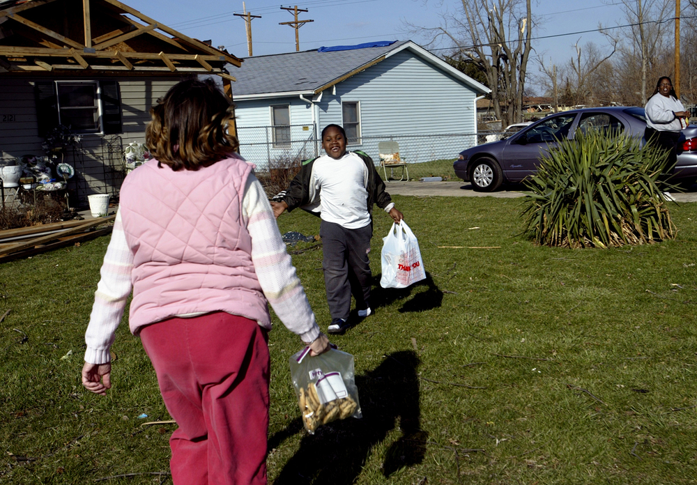 "Cortez Fort, 6, runs to accept a bag of cookies from Karen Dougherty on Spruce Street March 14, 2006. Dougherty, known as the ""cookie lady,"" made and delivered thousands of cookies to residents and workers in the tornado damaged areas. File/Jonathan Kirshner/The State Journal-Register"