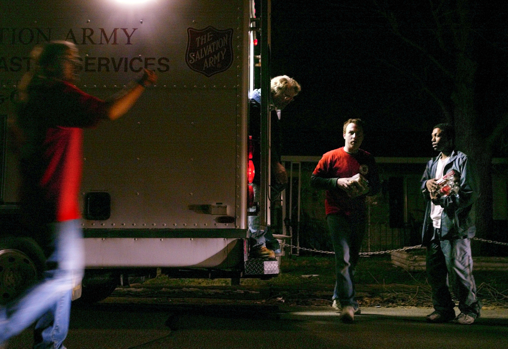 Springfield resident Dewann Miller, right, picks up some food and water from Salvation Army volunteer Dawn Price, maintenance manager Alan Sladek, and volunteer Chris Newton (left to right) as they distribute the goods around Springfield's east side neighborhood damaged by Sunday's tornados. File/ David Albers/The State Journal-Register
