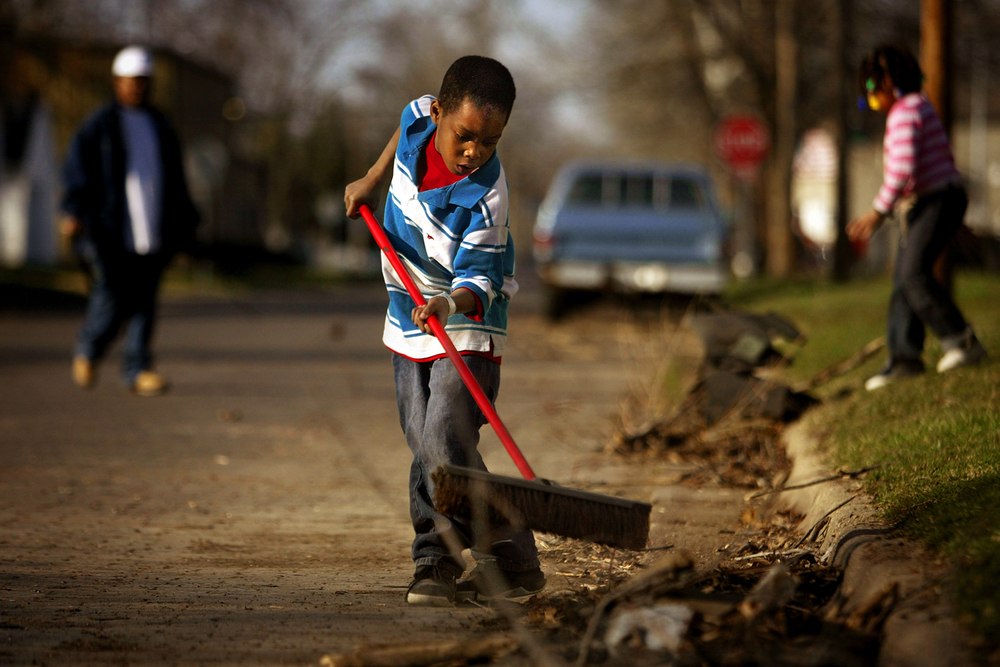 Ladarius Donald, 7, helps sweep up the last of the debris from his family's yard  on the corner of 19th and Cedar streets, Saturday, March 18, 2006.  David Albers/The State Journal-Register
