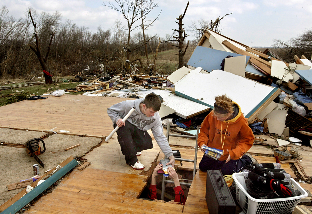 Mike Graves salvages personal items from his basement bedroom with the help of girlfriend Tiffany Workman, right, after Sunday's tornado destroyed the Peecher household on Lead Line Road near Loami. File/David Albers/The State Journal-Register