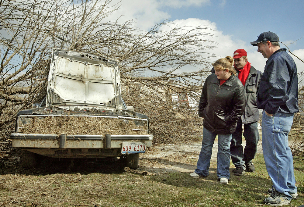 Friends and family members of the Peecher family examine how Sunday night's tornado damaged a car on the family's property near Loami. File/David Albers/The State Journal-Register