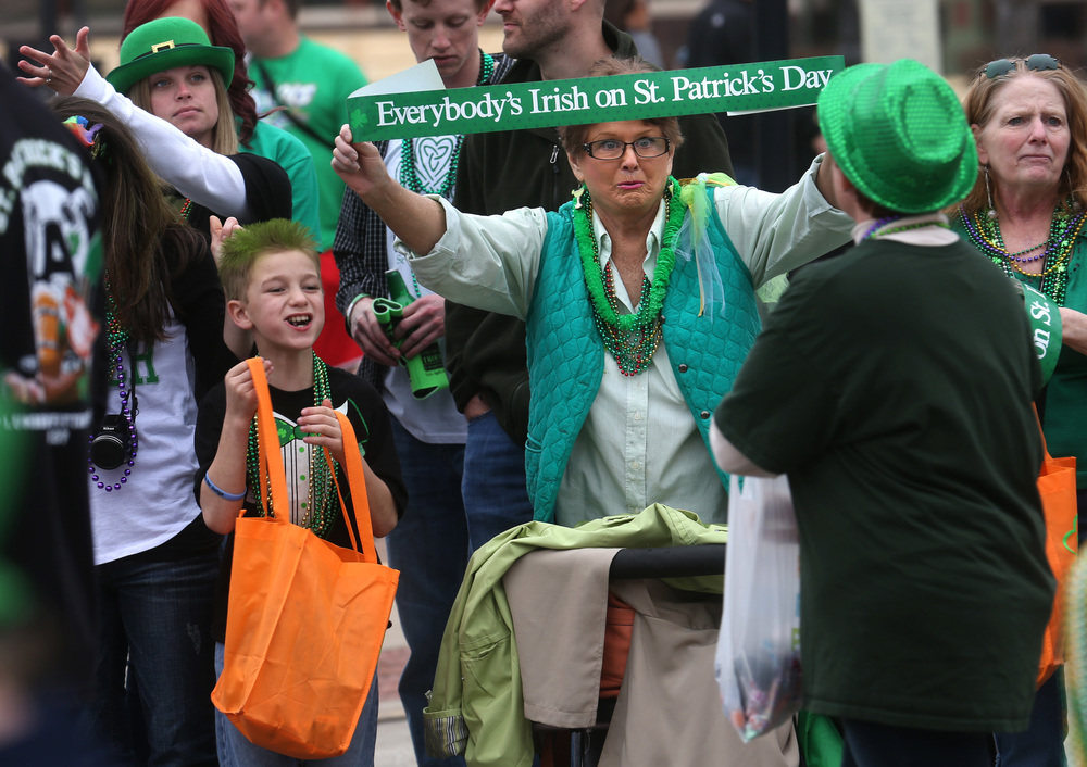 "New Berlin resident Helen Bridges, joined by daughter Katrina Hudgeons at right, holds out a banner along Jefferson St. proclaiming ""Everybody's Irish on St. Patrick's Day"". David Spencer/The State Journal Register"