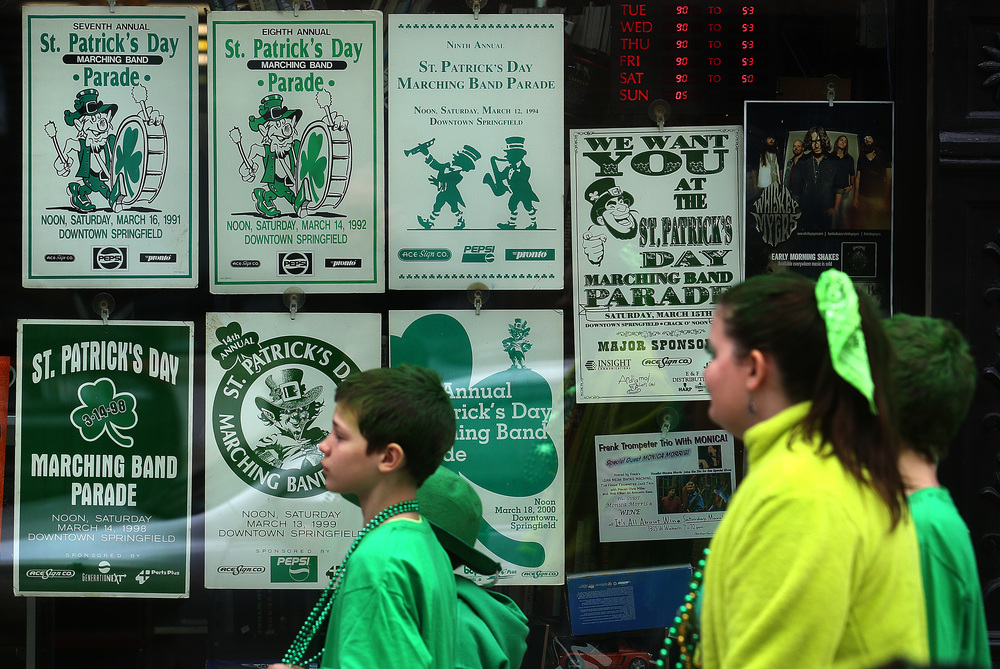 Parade-goers walk past a display of vintage Springfield St. Patrick's Day parade poster set up as a window display at Recycled Records in downtown Springfield before the start of the parade. David Spencer/The State Journal Register