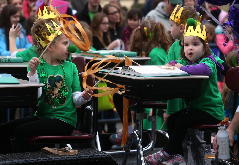 Students from Springfield's Christ the King school sit at desks set up on a float traveling in the parade Saturday. David Spencer/The State Journal Register