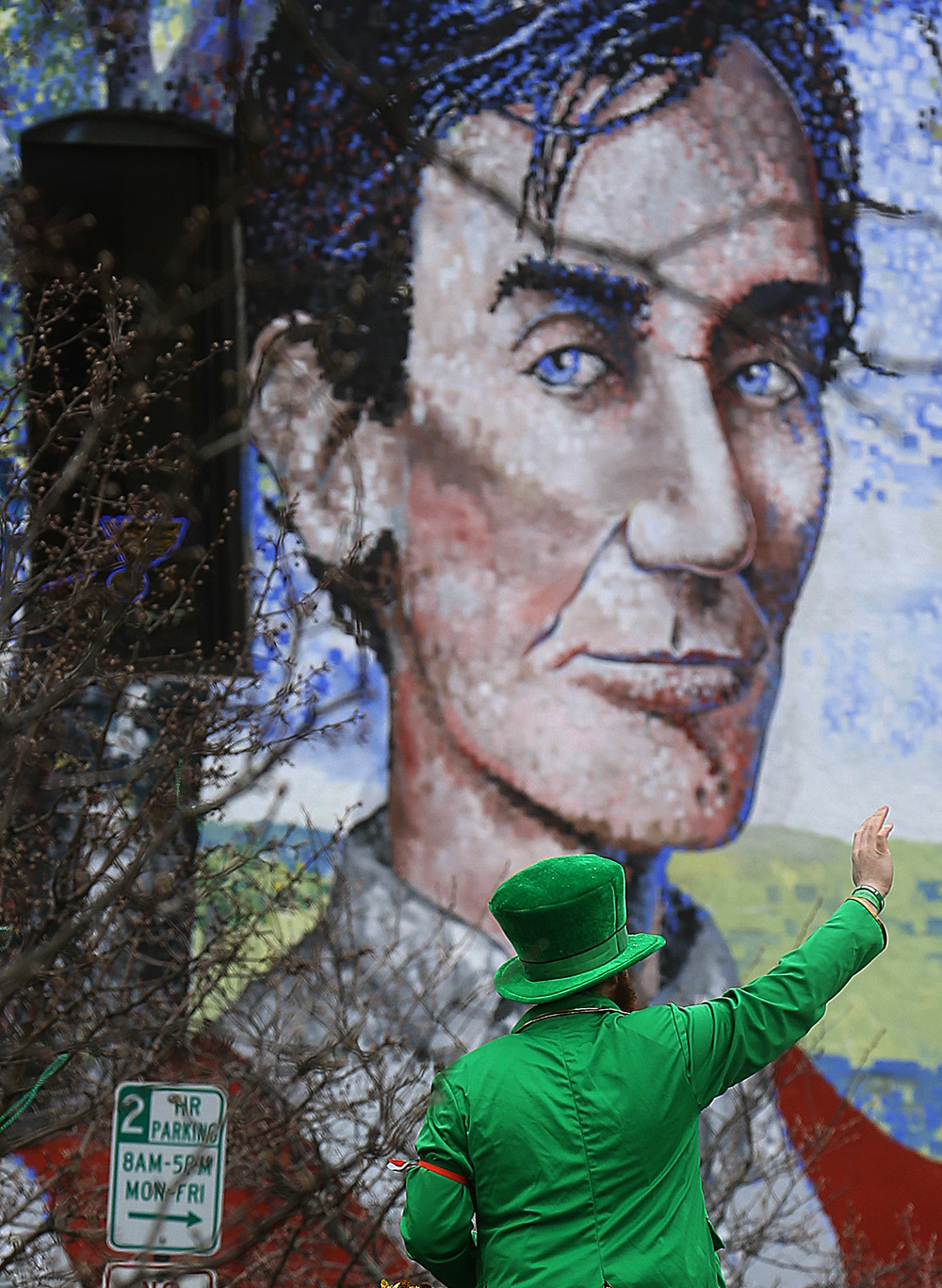 Ryan family leprechaun Trevor Parnell waves at the crowd as his float passes in front of the large mural of Abraham Lincoln on S. Fifth St. Saturday during the parade. David Spencer/The State Journal Register