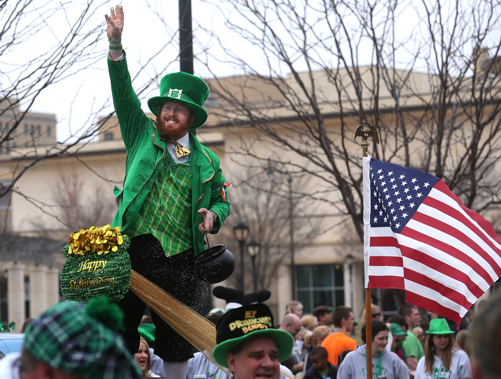 Playing the role of head leprechaun showering parade viewers and participants in gold dust was Ryan family float member Trevor Parnell of Springfield. David Spencer/The State Journal Register