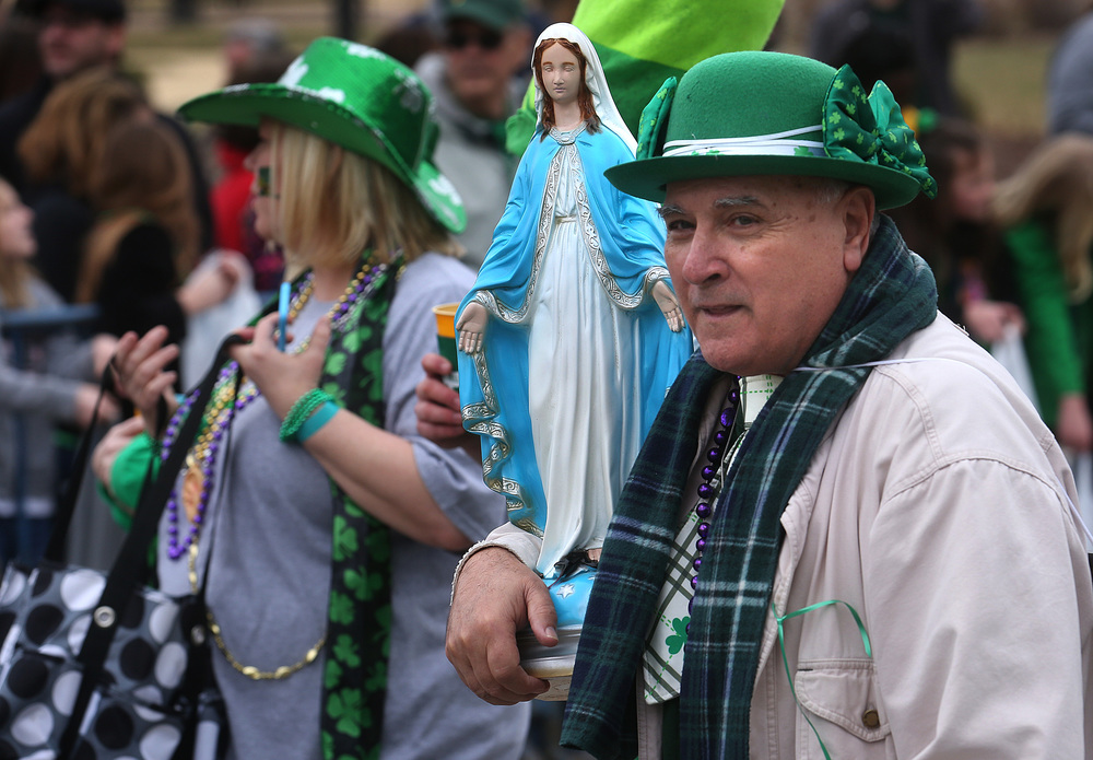 A member of the Legion of Mary at Springfield's Cathedral of the Immaculate Conception carries a statue of the Virgin Mary during the parade. David Spencer/The State Journal Register