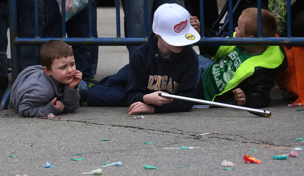 "And speaking of candy, one young parade goer at right came prepared with a ""grabber"". He waits with a buddy at left for some candy to come close by barricades set up along S. Fifth St.  David Spencer/The State Journal Register"
