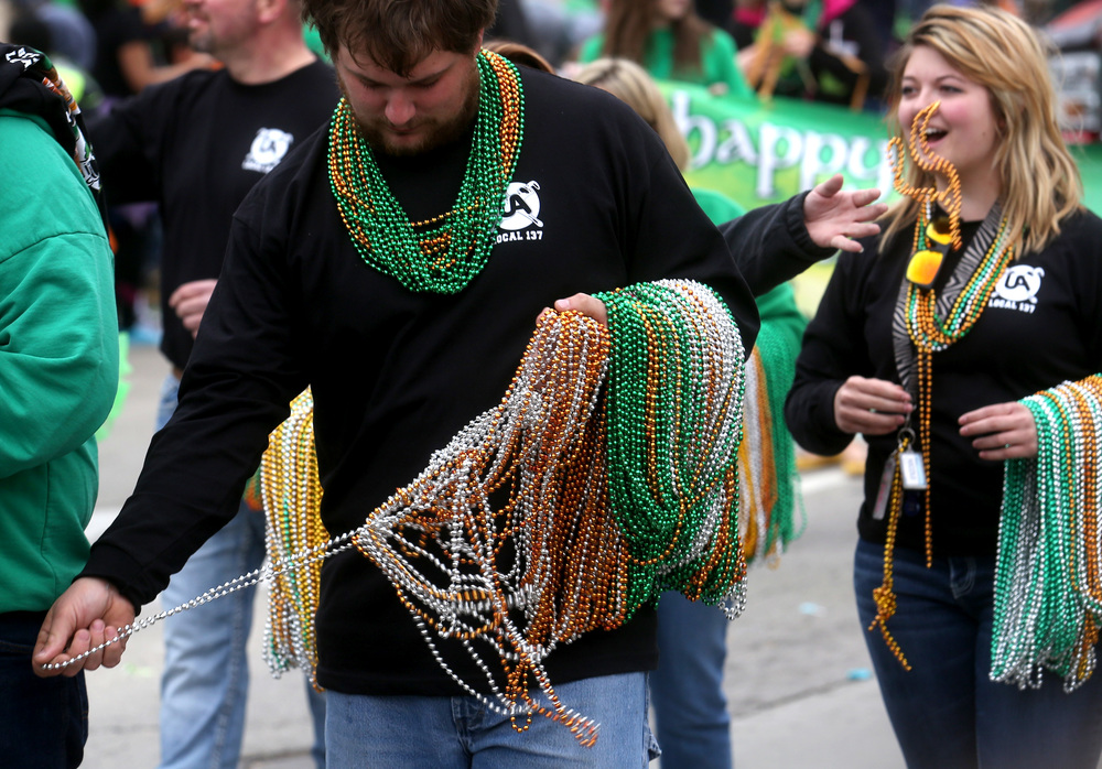 "Beads were also in abundance at this year's parade. A member of Plumbers & Steamfitters HVACR Local 137 had a bit of an entanglement problem however getting a few strands off his arm and into the crowd. With the theme of ""Family is Thee Pot o' Gold,"" the 32nd Annual St. Patrick's Day Parade took place in downtown Springfield on Saturday, March 12, 2016. The Langfelder family served as parade Grand Marshals. David Spencer/The State Journal Register"