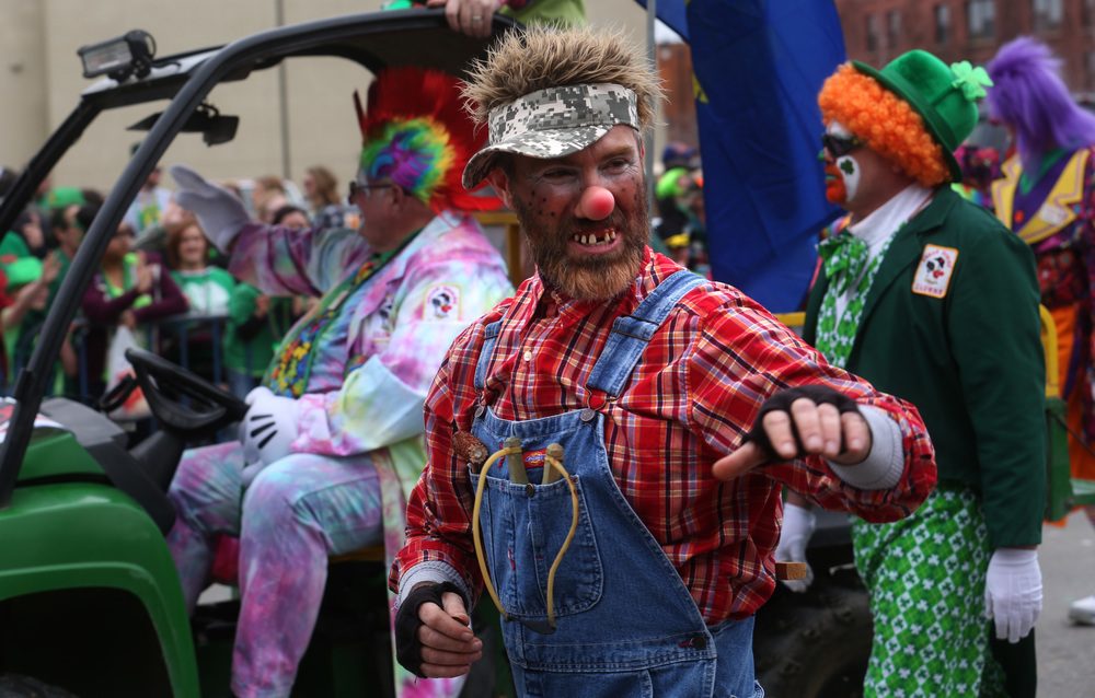 An Ansar Shrine clown waves and gives a toothy grin towards those watching the parade from behind barricades along S. Fifth St. Saturday.  David Spencer/The State Journal Register