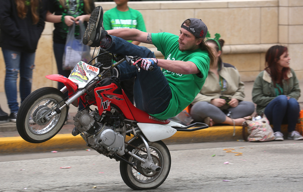 A member of the 217 Fiddy Crew mini-bike stunt group rides a wheelie along Jefferson St. on Saturday. David Spencer/The State Journal Register