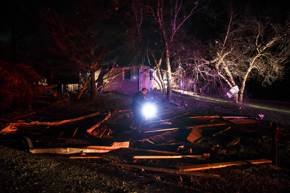 A Sangamon County Sheriff's deputy goes through debris in the front yard of a structure in the 6300 block of West Iles Avenue that was hit by a suspected tornado, Tuesday, March 15, 2016, in Springfield, Ill. Justin L. Fowler/The State Journal-Register