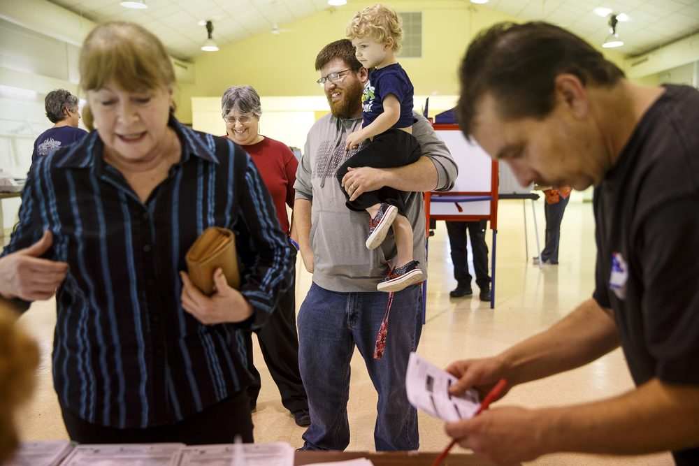 Matt Kelley and his son Cillian wait in line to get their ballot at the Grandview Municipal Building Tuesday, March 15, 2016. Ted Schurter/The State Journal-Register