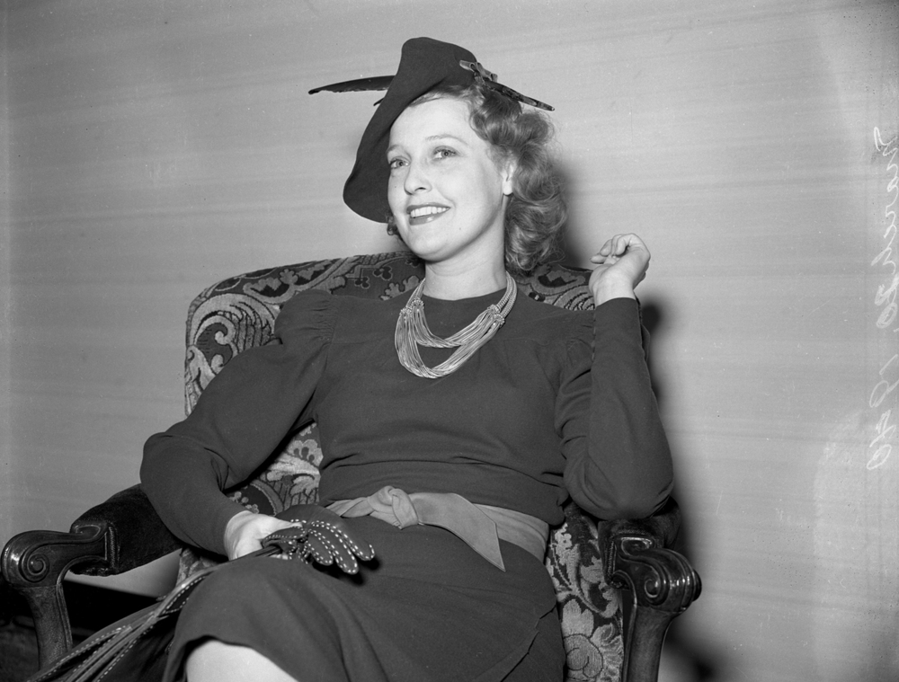 "Jeanette MacDonald answers questions from reporters during a press conference in her hotel room at the Leland Hotel. She said she hoped to take a brief walk to the Lincoln sites before her evening performance at The Orpheum Theater. The red-haired actor/singer described the color of the dress she wore as ""MacDonald"" rust. File/The State Journal-Register"