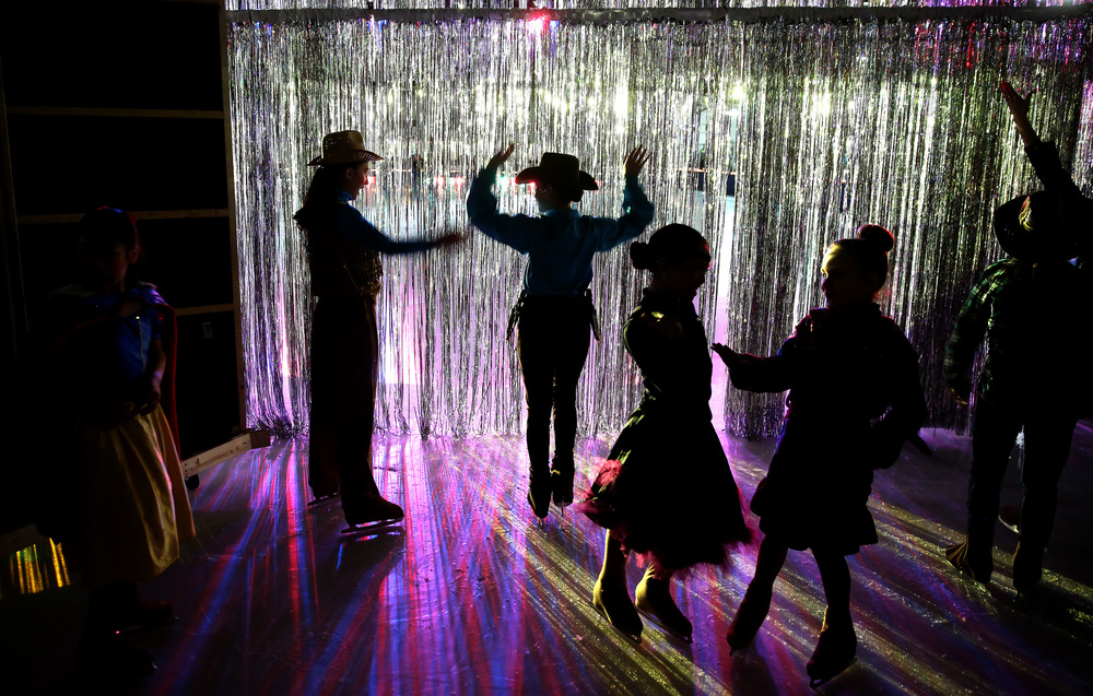 Young skaters take a peek through the curtain separating backstage and the show area before the start of Saturday's matinee performance. David Spencer/The State Journal Register