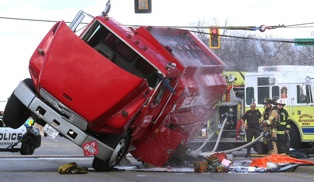 Sherman firefighters were on standby in background as water from a firehose is sprayed on the gas truck while the truck was uprighted by a wrecker on Thursday, March 17, 2016. A Nelson Oil Co. of Springfield gas truck carrying about 1,000 gallons of diesel fuel overturned along Business 55 in Sherman on Thursday, prompting authorities to close all lanes of the busy roadway. The driver of the vehicle, who was unhurt, told authorities the accident was the result of a mechanical problem. About 50 gallons of diesel fuel spilled from the truck, but emergency responders were able to catch some of the fuel in a plastic container. David Spencer/The State Journal Register