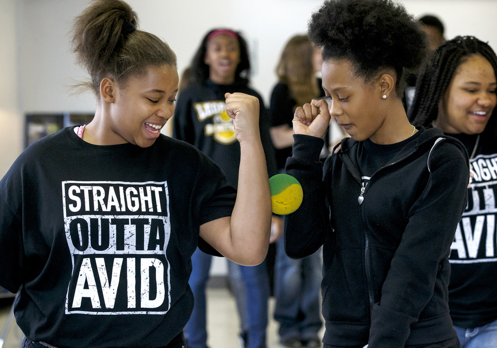 Seventh graders Brehshaunti Hodges, left, and Jasmine Tyler, right, walk through the room trying to keep a ball from falling from between their arms without touching it in an exercise about learning to collaborate with others during Carlie Erickson's Advancement Via Individual Determination, AVID, class at Lincoln Magnet School, Thursday, March 24, 2016, in Springfield, Ill. Justin L. Fowler/The State Journal-Register