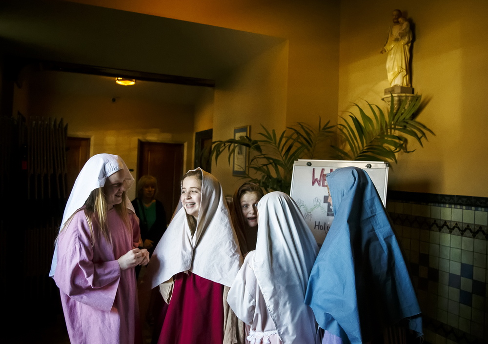 Elise Huffstedtler, center, gathers with her fellow seventh graders at the entry way to Blessed Sacrament Church as they play the roles of the village ladies that attendees see as they enter the sanctuary for Blessed Sacrament's Seventh Grade presentation of The Living Stations of the Cross, Friday, March 25, 2016, in Springfield, Ill. Justin L. Fowler/The State Journal-Register