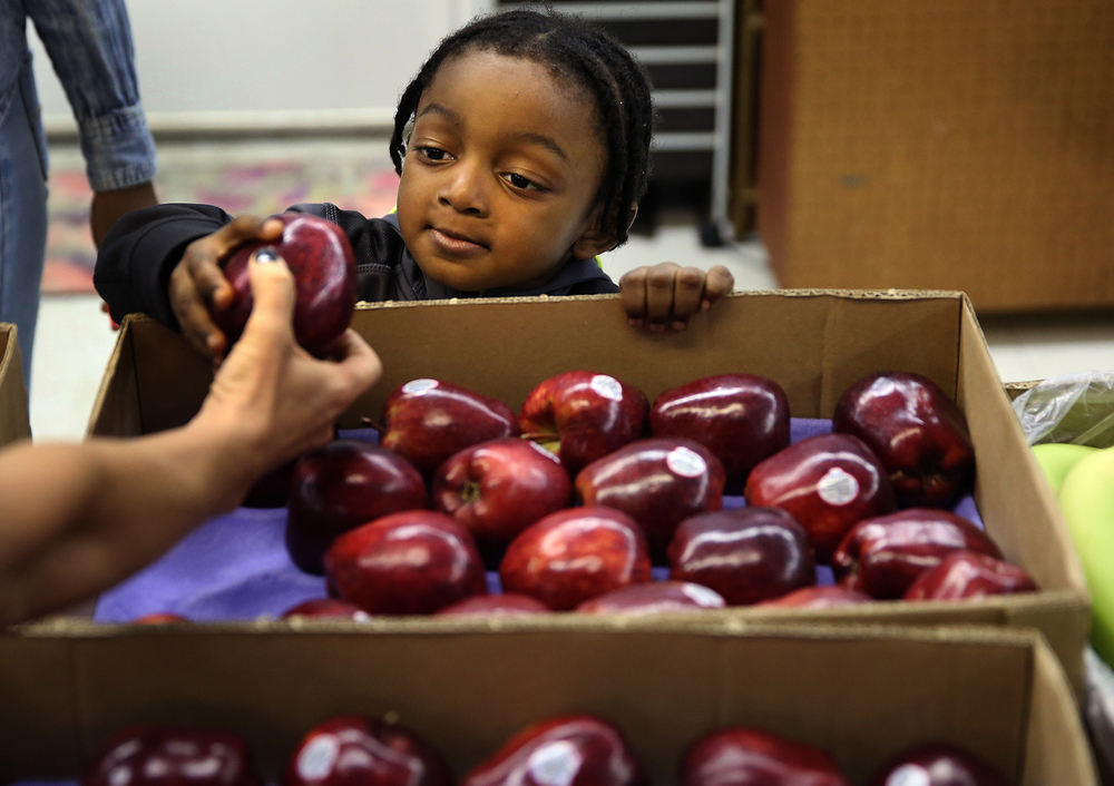 Andreas Tynes, 2, reaches for an apple presented to him at the pantry by Tom Lange Company employee Becky Wilson on Thursday. A wholesaler in fruits and vegetables, the Springfield company donated fresh fruit for the pantry. Staffed by volunteers from Illinois National Bank, the Central Illinois Foodbank held their sixth annual kids snack food pantry at Brandon Court housing complex in Springfield on Thursday, March 24, 2016. The event was held before the start of Spring break so the 150-200 children who participated could have fresh food, including fruit, bread, milk as well as snacks and other easily prepared food as well as an Easter basket for the break. David Spencer/The State Journal Register
