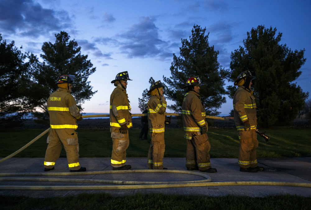 The sun begins to set as firefighters from Williamsville and Sherman line up in their positions during an exercise designed to teach firefighters how to handle liquid propane fires presented by the Illinois Fire Service Institute at the Sherman fire station, Thursday, March 31, 2016, in Sherman, Ill. Each firefighter plays a role in ensuring not only that the fire is extinguished, but that they remain safe in the process. Justin L. Fowler/The State Journal-Register