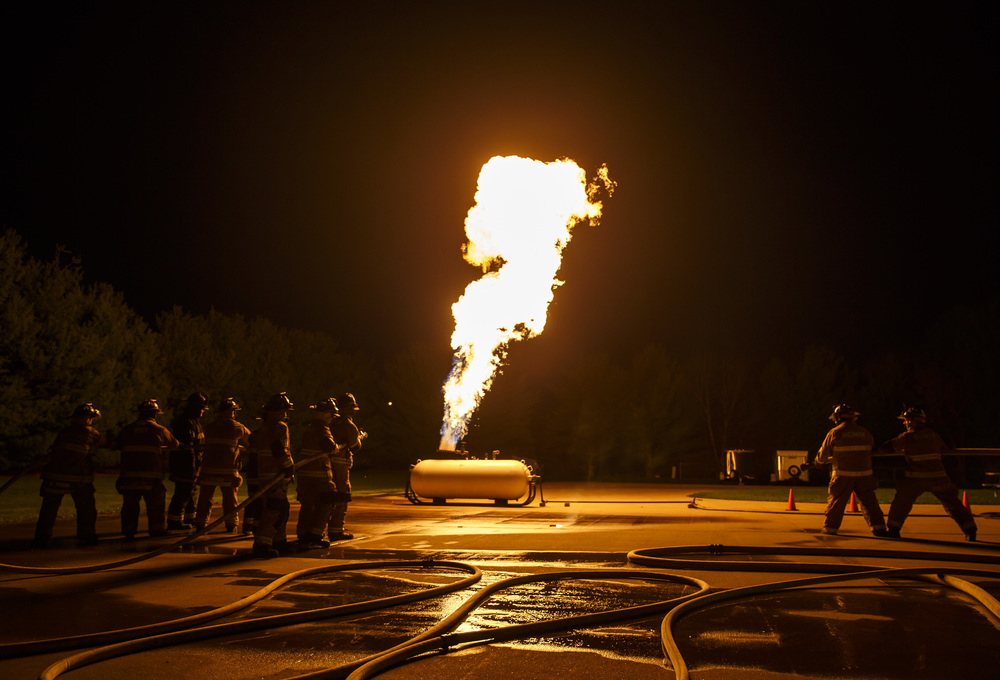 Two lines of firefighters, on the left, begin their attack on a controlled propane fire during an exercise designed to teach firefighters how to handle liquid propane fires presented by the Illinois Fire Service Institute at the Sherman fire station, Thursday, March 31, 2016, in Sherman, Ill. Justin L. Fowler/The State Journal-Register