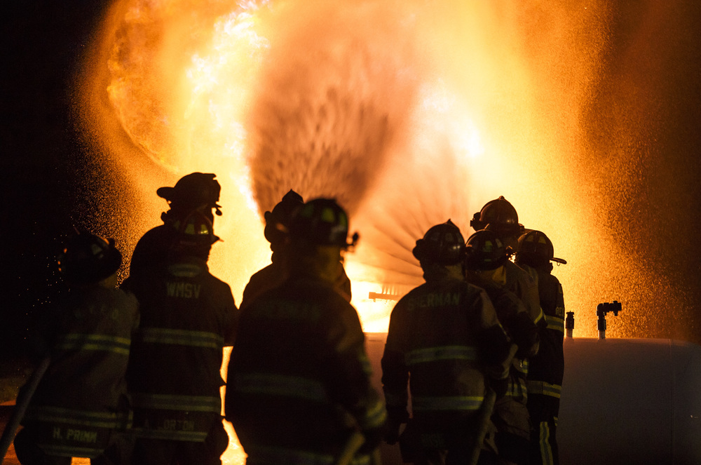 Firefighters from Williamsville and Sherman use two lines to direct streams of water in a pattern to extinguish a controlled propane fire during an exercise designed to teach firefighters how to handle liquid propane fires presented by the Illinois Fire Service Institute at the Sherman fire station, Thursday, March 31, 2016, in Sherman, Ill. Justin L. Fowler/The State Journal-Register