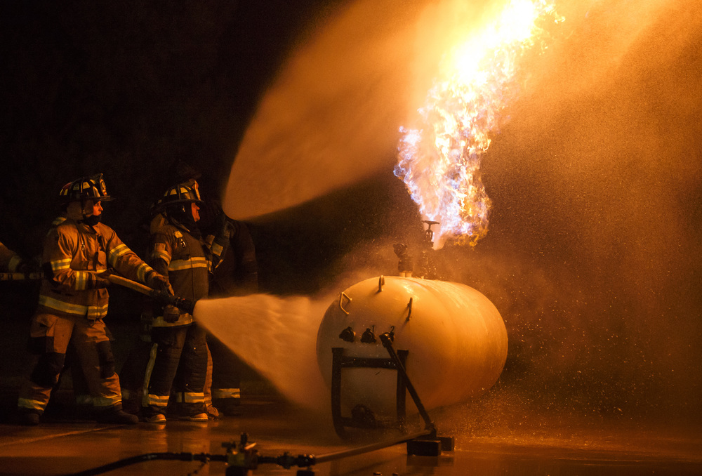 Firefighters from Williamsville and Sherman attack a controlled propane fire with two separate lines during an exercise designed to teach firefighters how to handle liquid propane fires presented by the Illinois Fire Service Institute at the Sherman fire station, Thursday, March 31, 2016, in Sherman, Ill. Justin L. Fowler/The State Journal-Register