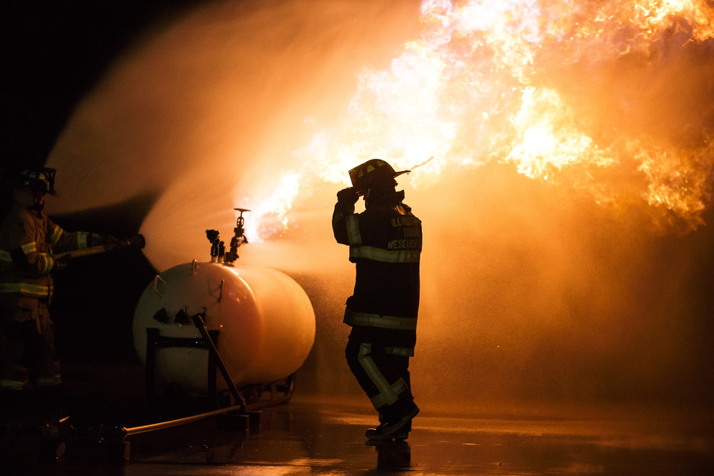 An instructor adjusts his hat as he walks back from retrieving a flare used to ignite a controlled propane fire during an exercise designed to teach firefighters how to handle liquid propane fires presented by the Illinois Fire Service Institute at the Sherman fire station, Thursday, March 31, 2016, in Sherman, Ill. Justin L. Fowler/The State Journal-Register