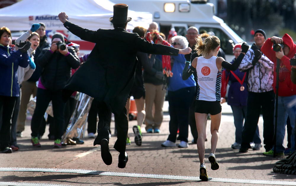 Emily Kunan of Petersburg, the top women's finisher, broke the finish line along with Abraham Lincoln (Michael Krebs of Chicago) Saturday morning in downtown Springfield. David Spencer/The State Journal Register