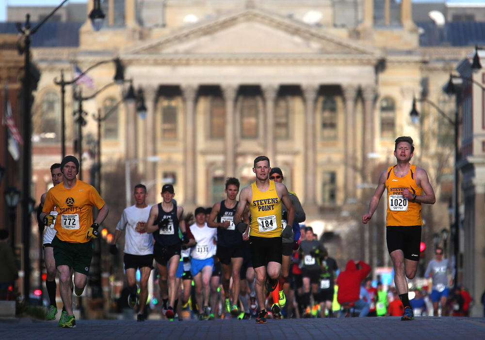 The front of the pack sprints east on Capitol Ave. towards the Lincoln Home near the start of the race with the state Capitol building as a backdrop. David Spencer/The State Journal Register