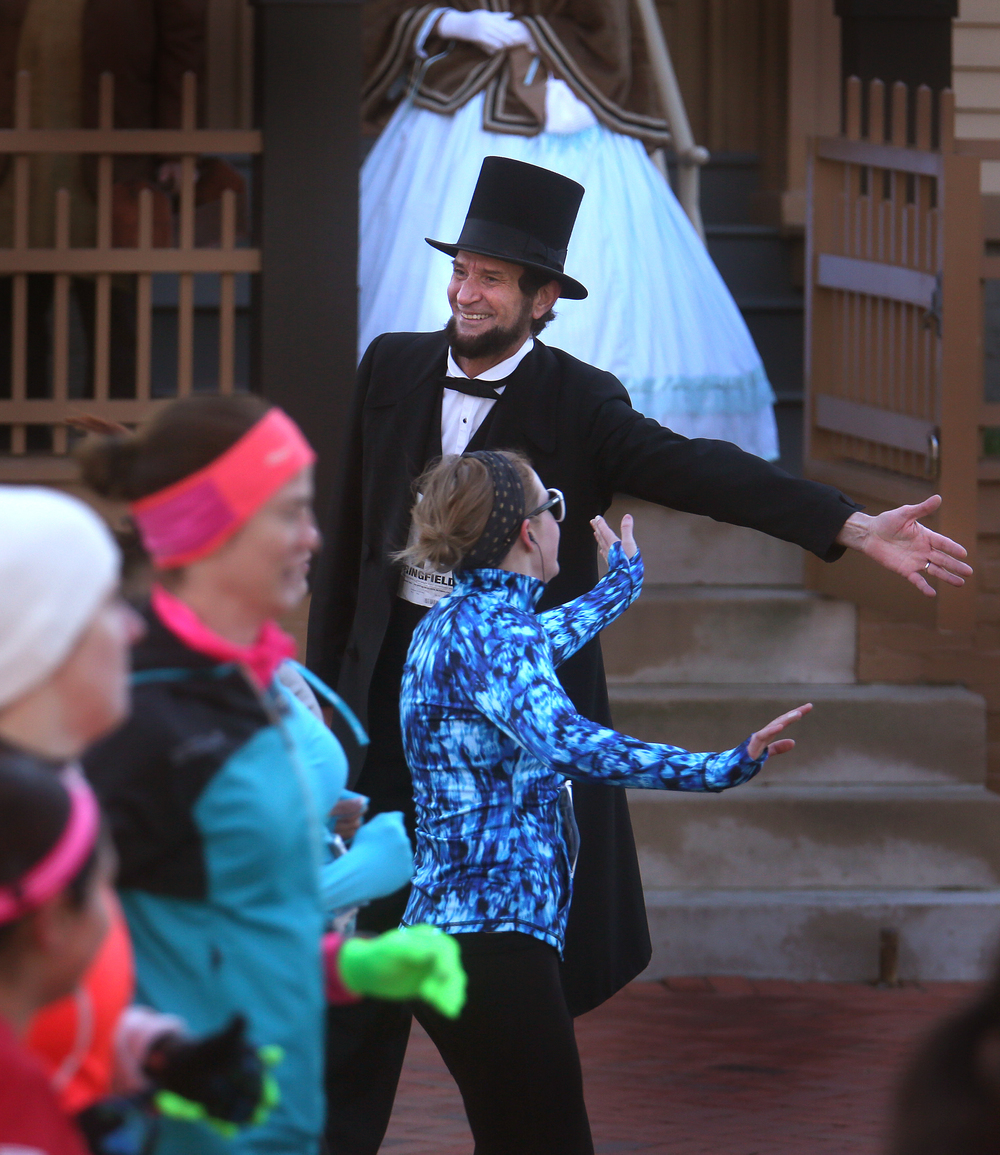 Abraham Lincoln (Michael Krebs of Chicago) offered a low-five as runners passed by the front of his home in Springfield early Saturday morning. David Spencer/The State Journal Register