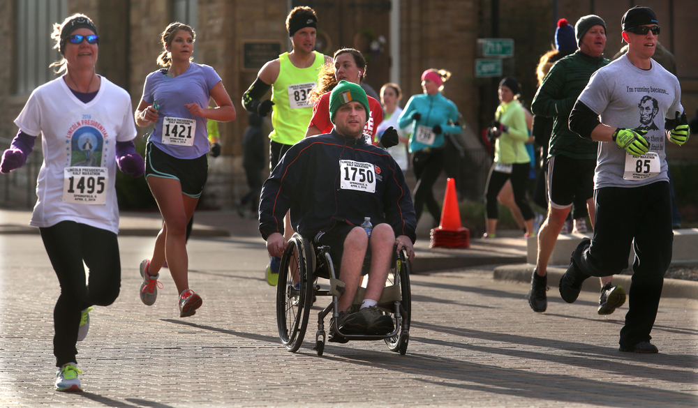 Wheelchair competitor Brian Sheehan ended up finishing in 2:11:34. He and other runners make their way west on Capitol Ave. early Saturday morning. David Spencer/The State Journal Register