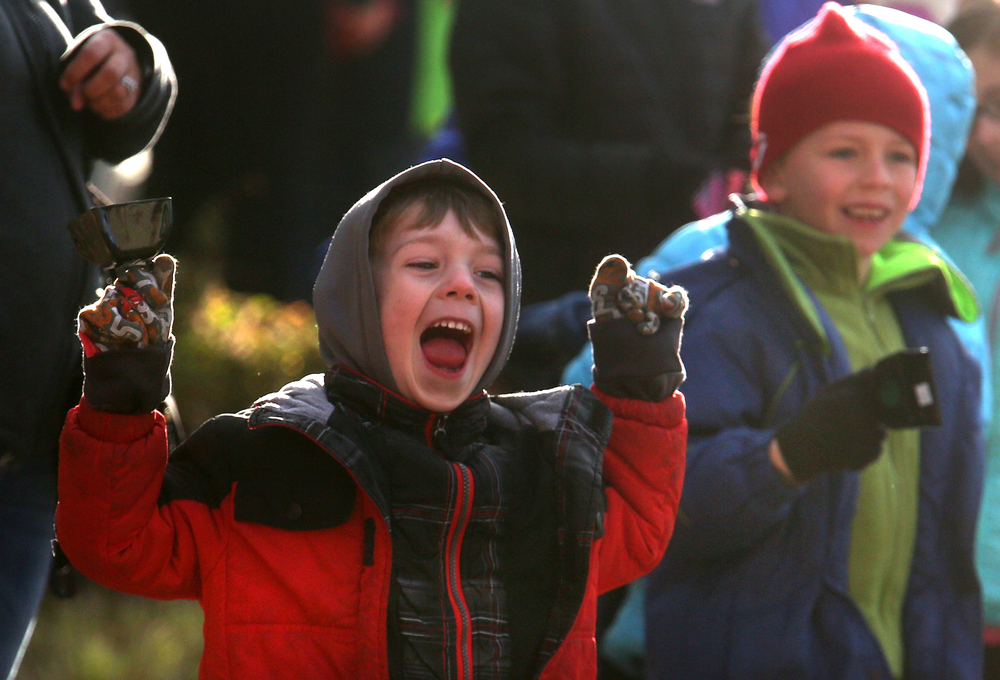 A child gets excited while ringing a cowbell as runners make their way west on Capitol Ave. early Saturday morning. David Spencer/The State Journal Register