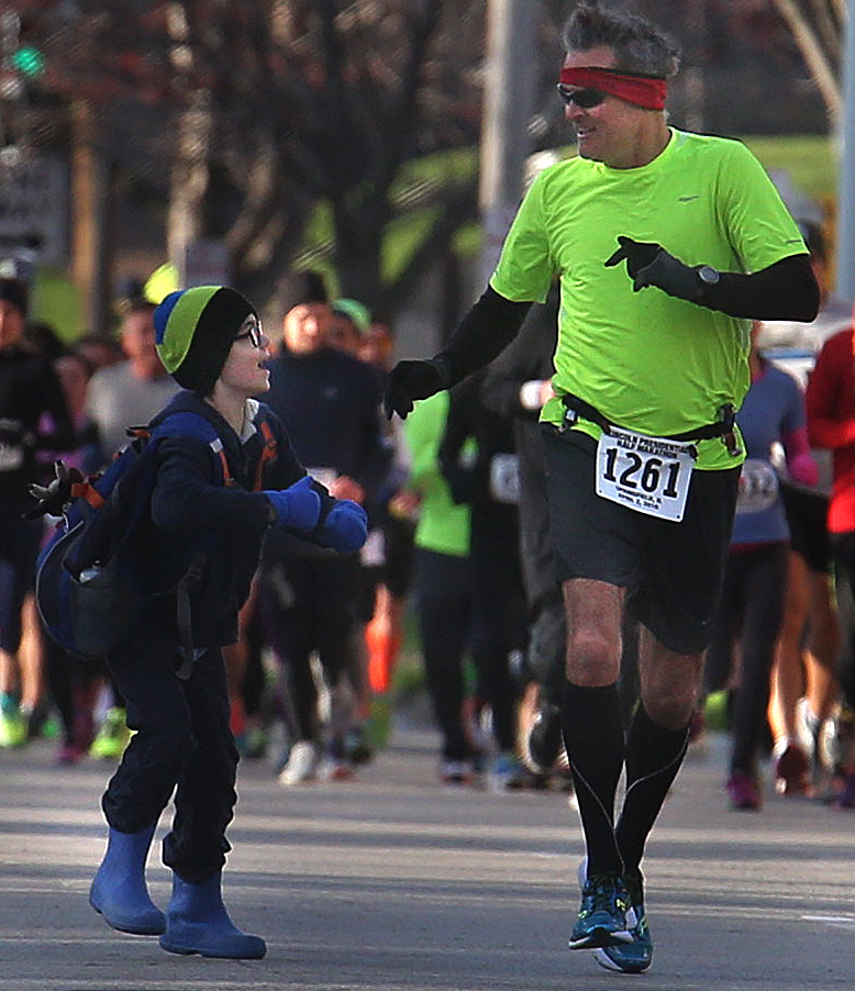 Runner Chris Schade of Cincinnati, OH was greeted along the race route while making his way north on Seventh St. early Saturday morning. David Spencer/The State Journal Register