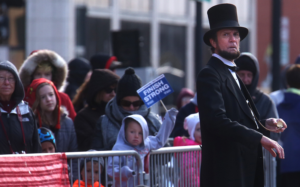 Abraham Lincoln (Chicago's Michael Krebs) checks his pocket watch as he spies runners making their way to the finish line where he stood. David Spencer/The State Journal Register