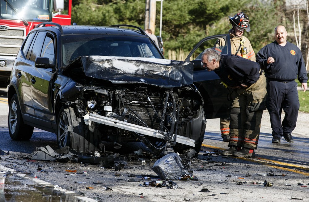 Firefighters from Springfield and Chatham responded to the scene of a two-vehicle accident in the 1300 block of Woodside Road, Monday, March 28, 2016, in Springfield, Ill. Four people, including two children, were taken to the hospital Monday afternoon following the crash where an SUV rear ended another SUV and caught fire after the driver exited. Justin L. Fowler/The State Journal-Register