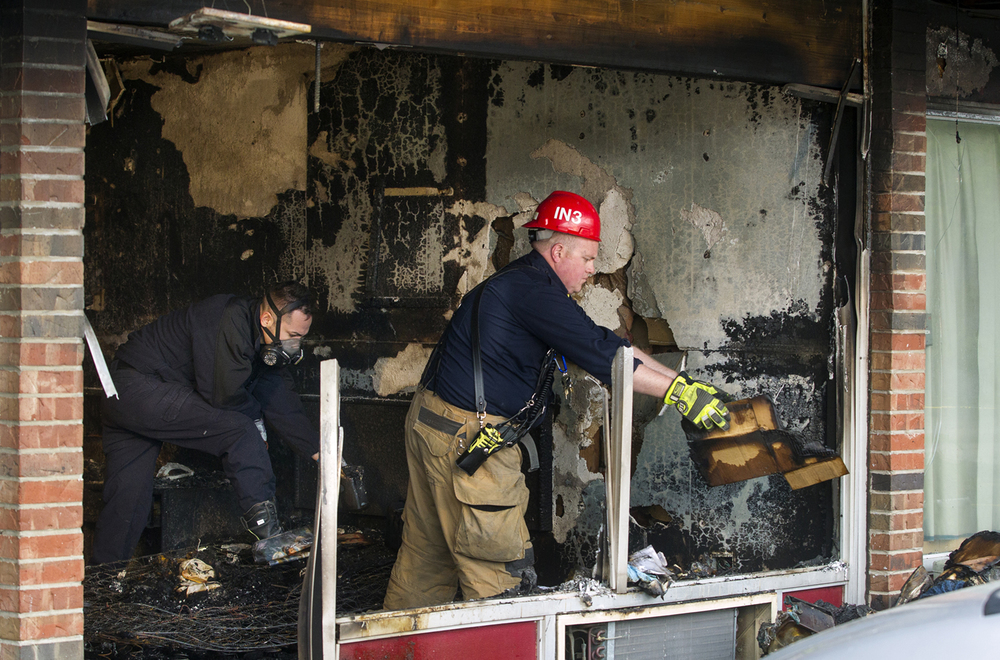 Fire investigators sift through the contents of a hotel room at the Stevenson Inn after an early morning fire left one woman dead Friday, April 1, 2016. Ted Schurter/The State Journal-Register