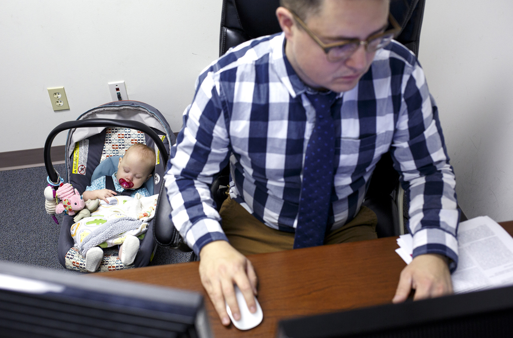 Josh Catalano works while his daughter, Harper, sleeps in his office at an association management firm in Springfield, March 28, 2016. Catalano says she's at the office with him for an hour or two, once or twice a month when his and his wife's schedules are in transition. Rich Saal/The State Journal-Register