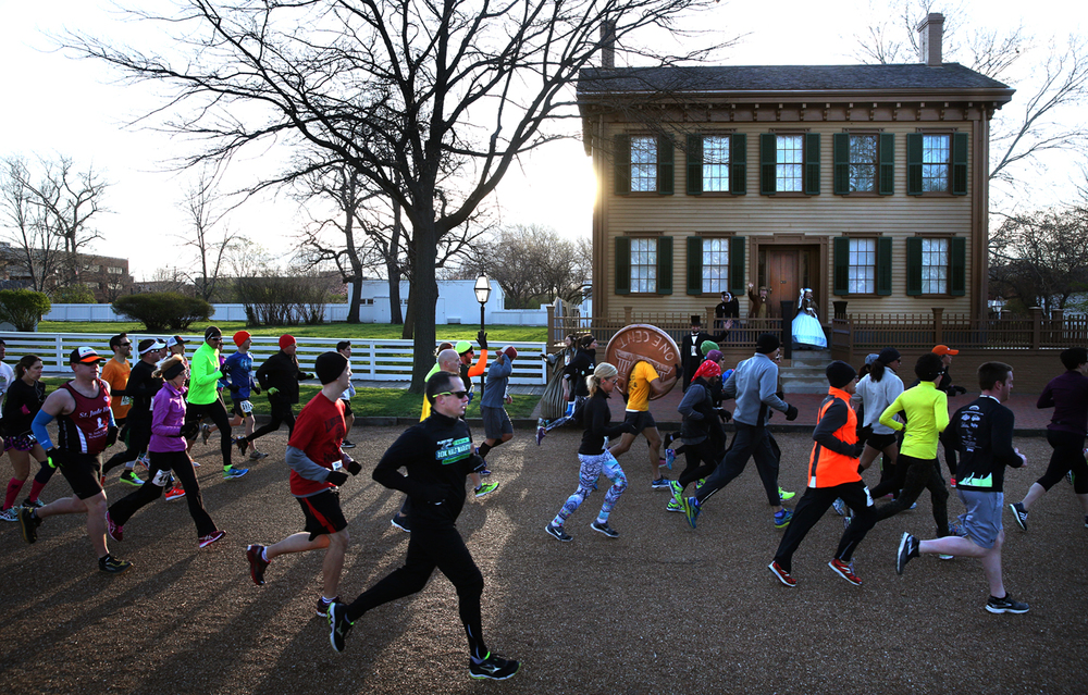Participants run past the Lincoln Home near the start of the Lincoln Presidential Half Marathon early Saturday morning. David Spencer/The State Journal Register