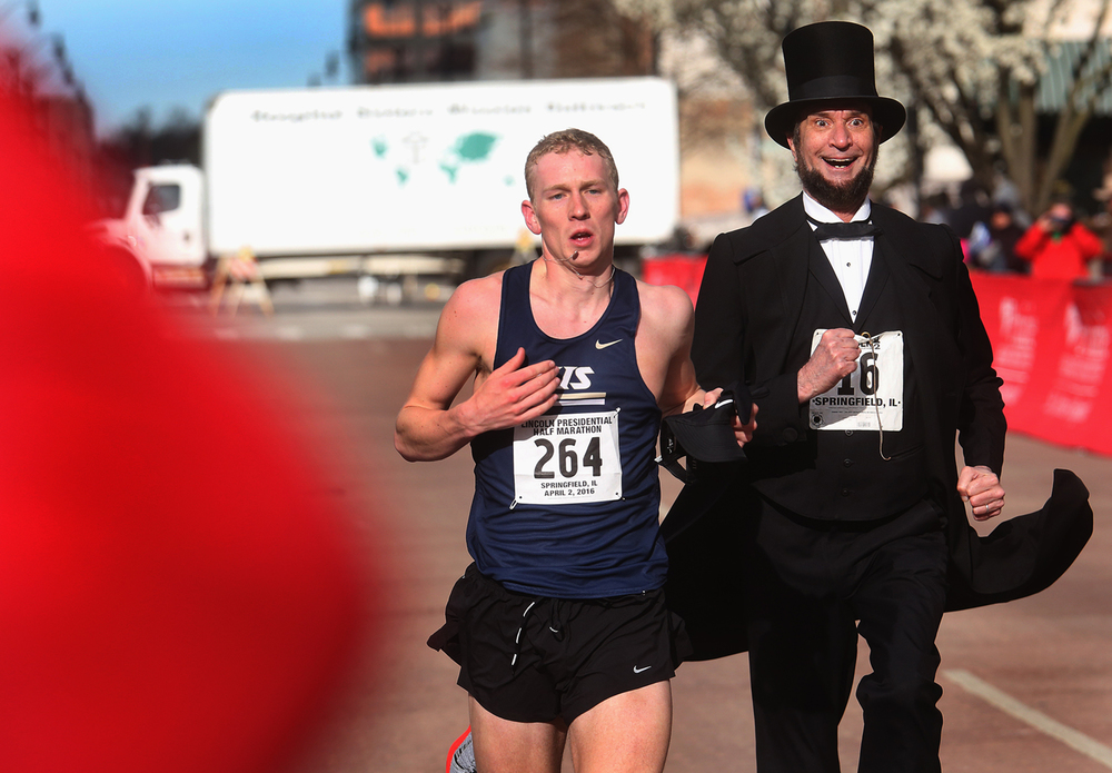 Lincoln Presidential Half Marathon top men's finisher Eli Cook of Rochester, a sophomore at UIS, was joined by Abraham Lincoln (Michael Krebs of Chicago) at the finish line Saturday line. David Spencer/The State Journal Register