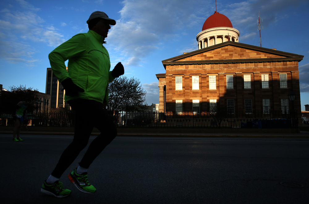Runners warm up in downtown before the start of the Lincoln Presidential Half Marathon, with the the Old State Capitol as an early morning backdrop. David Spencer/The State Journal Register