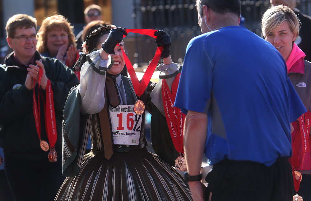 Mary Todd Lincoln (Debra Ann Miller of Chicago) prepares to place a medal around the neck of a finisher Saturday at the Lincoln Presidential Half Marathon. David Spencer/The State Journal Register