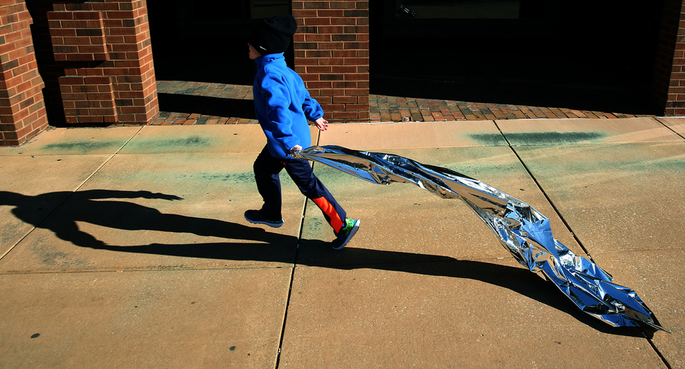 A child runs with a thermal Mylar blanket that some of the runners used to warm up with at the conclusion of the Lincoln Presidential Half Marathon on Saturday in downtown Springfield. David Spencer/The State Journal Register