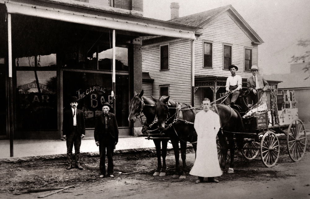 A horse-drawn Reisch Brewing Co. delivery wagon is parked outside the Capital Bar in Springfield around 1900 or before. The gentleman standing at front is most likely the proprietor of the establishment, with the wagon decorated in a patriotic theme, probably for the Fourth of July. Photograph courtesy Sangamon Valley Collection at Lincoln Library