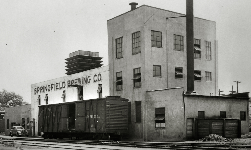 "An exterior view of the Springfield Brewing Company with a rail car on the 10th street tracks being unloaded. The photo probably dates to the mid to late 1930's. Immediately after Prohibition ended in 1933, a new brewery, The Springfield Brewing Company, headed up by Chicago businessman Nicholas A. Schlangen, set up shop in buildings located at 11th and Madison streets. According to a 2009 issue of the magazine Beer Cans & Brewery Collectibles held in Lincoln Library, the new brewery produced its first beer, ""Archer,"" available only on draft, on October 25, 1933. Conrad Engelking became president of the brewery in 1934 and eventually a beer was named after him: ""Engelking's"". The firm embraced marketing in a big way and did contract brewing for other brands shipped out of state. The brewery ceased operations in 1947. Photograph courtesy Sangamon Valley Collection at Lincoln Library"